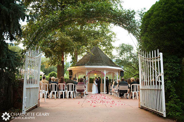 Archway covered in greenery for a gazebo wedding in a courtyard