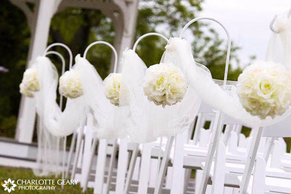 Aisle decorated white white flowers and tulle hung from shepherds hooks