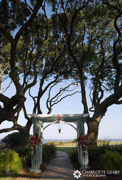Ceremony arch decorated with flower arrangements and hanging vase