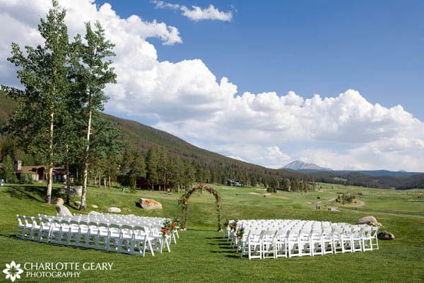 Ceremony site set up with white chairs and a floral arch