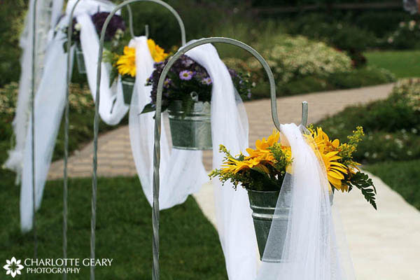 Yellow and purple daisies in silver buckets, hung from shepherds hooks