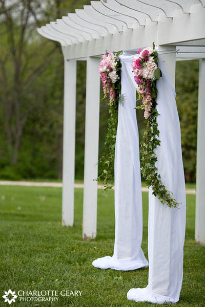 Pink and green floral arrangements hung from wedding altar