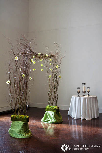 Ceremony archway made of curly willow and hanging green orchids