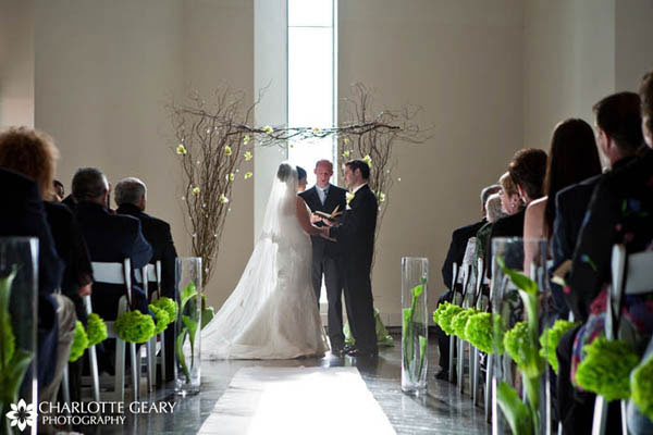 Ceremony aisle lined with green paper tissue balls and tall hurricane vases filled with green calla lilies