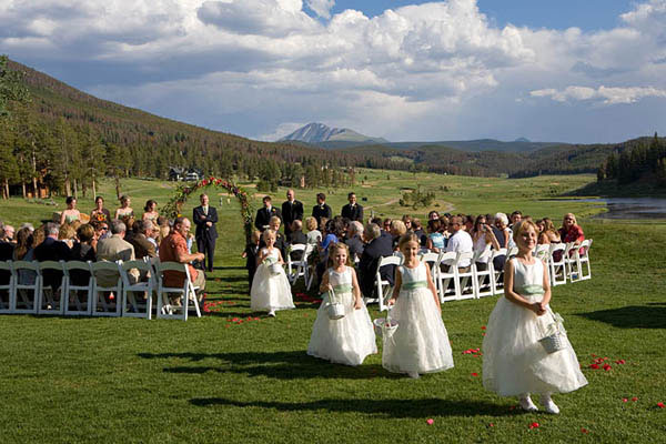 Flower girls in white dresses with light green sashes