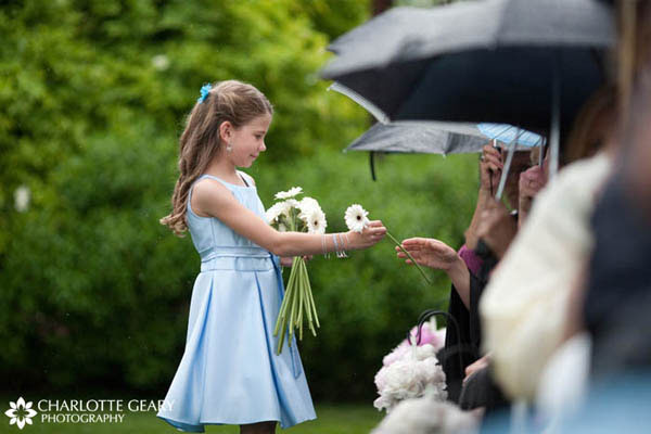 Instead of tossing flower petals, this flower girl handed out flower to the guests as she walked down the aisle.