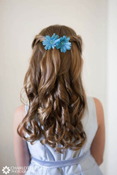 Flower girl with blue flowers in her half-up hairstyle