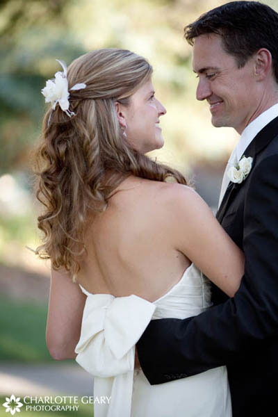Bride with curls and white flowers in her half-up hairstyle