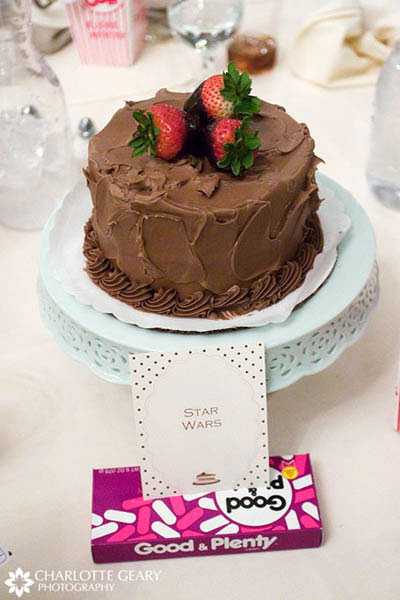 Small cake as a centerpiece on each table, with a table name card displayed in movie candy at a movie-themed wedding