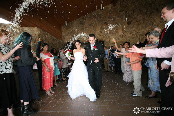 Guests tossing rice as the bride and groom depart