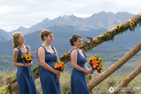 Bridesmaids in blue dresses with orange flowers