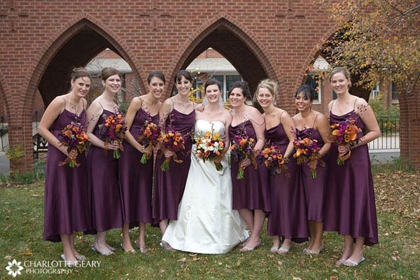 Bridesmaids in purple dresses with orange and purple flowers