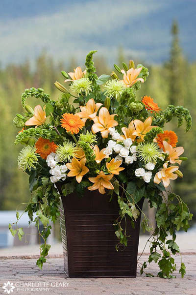 Flower arrangement of yellow and orange lilies and daisies