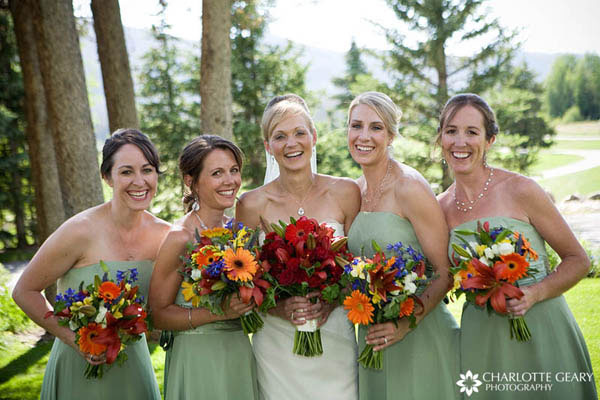 Bridesmaids in light green dresses with colorful bouquets