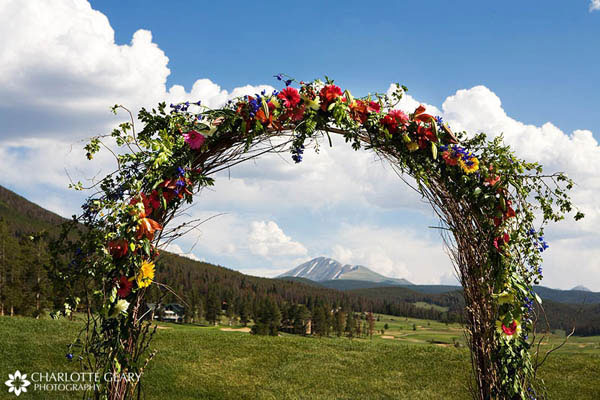 Wedding ceremony arch decorated with colorful wildflowers