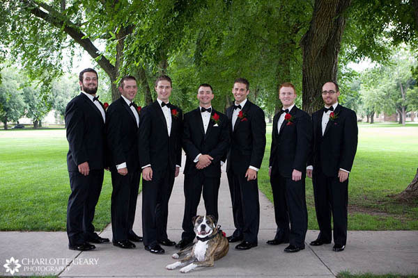 Groomsmen in tuxedos with red boutonnieres