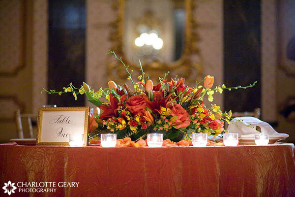 Sweetheart table with orange tablecloth and orange and red centerpiece