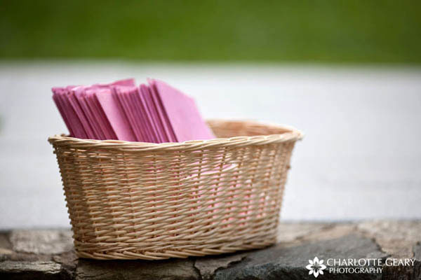 Pink wedding programs displayed in a wicker basket