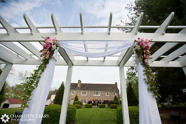 Trellis decorated with pink flowers and white tulle
