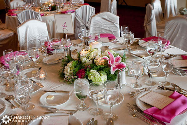 Wedding reception table set with pink linens and a pink and green centerpiece
