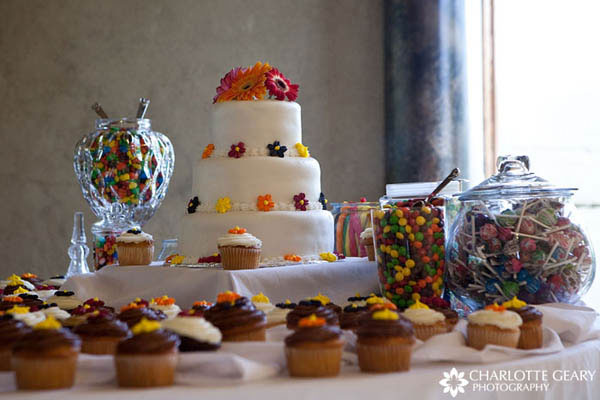 Wedding cake displayed with a candy buffet and cupcakes