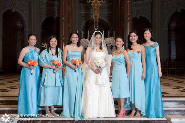 Bridesmaids and wedding sponsors in turquoise dresses with orange flowers