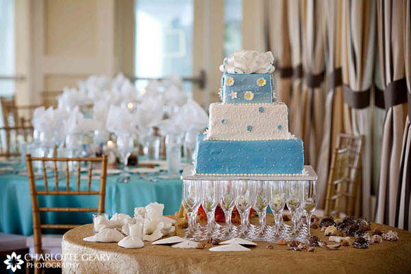 Blue and white wedding cake displayed on champagne glasses
