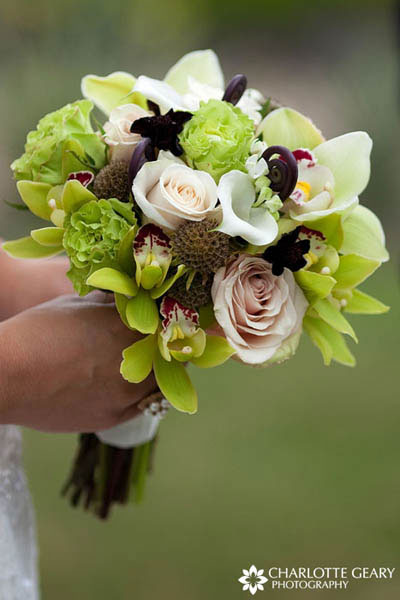 Bridal bouquet with green orchids, pink roses, and brown fiddlehead ferns
