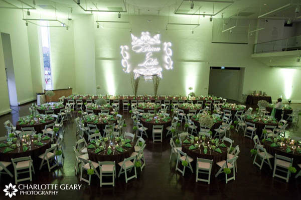 Reception room decorated with green and brown table linens and green up-lighting