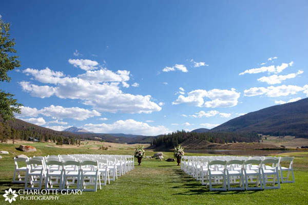 Wedding ceremony decorated with white chairs and flower arrangments