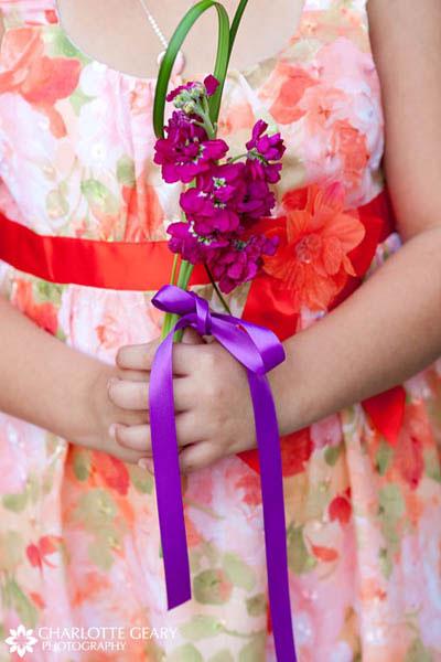Flower girl in orange dress with purple flowers