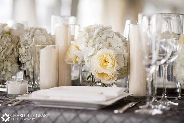 Table decorated with white flowers and candles and a silver tablecloth
