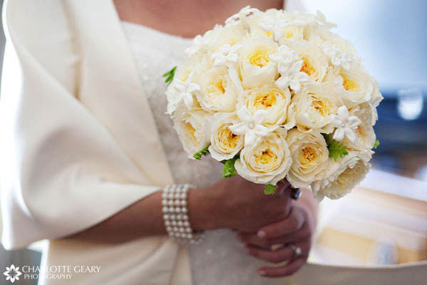 Bride with white bouquet of roses and stephanotis