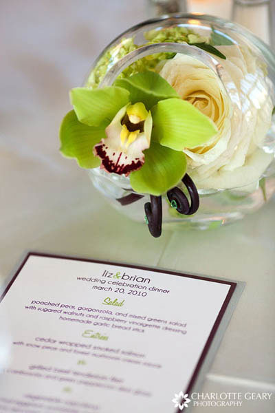 Green orchid centerpiece in a glass bowl with a green and purple menu card