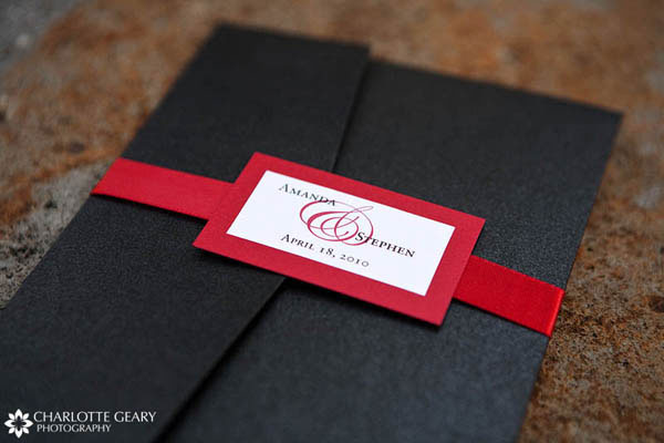 Red, black, and white wedding invitation with monogrammed ribbon tag