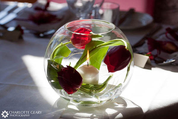 Red tulips and candle in a glass bowl