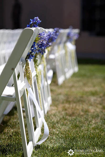 Blue flowers tied to wedding ceremony chairs