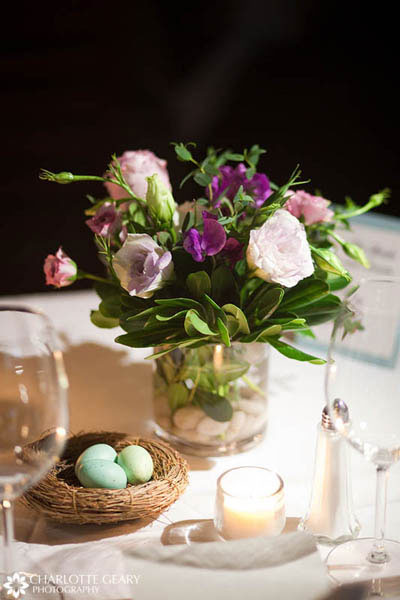 Purple centerpiece with birds nest at a lovebird themed wedding