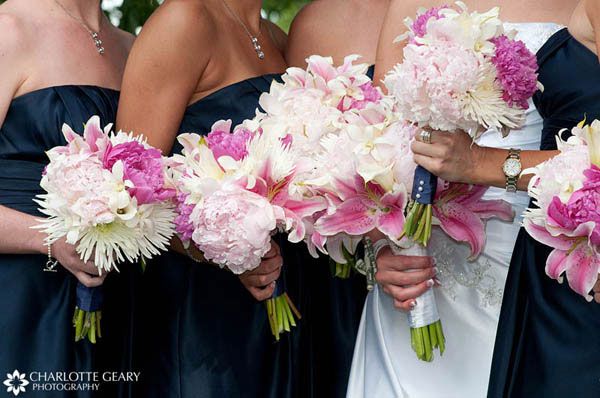 Bridesmaids with navy dresses and pink bouquets