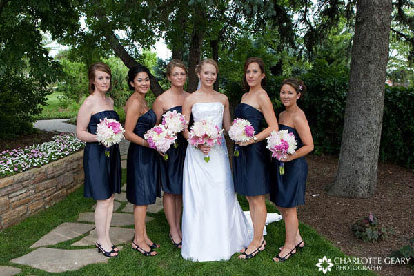 Bridesmaids in strapless navy blue dresses with pink bouquets