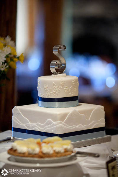 Mountain-themed wedding cake with blue ribbons and a monogram topper