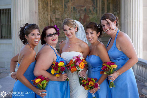 Bridesmaids in bright blue dresses with orange flowers