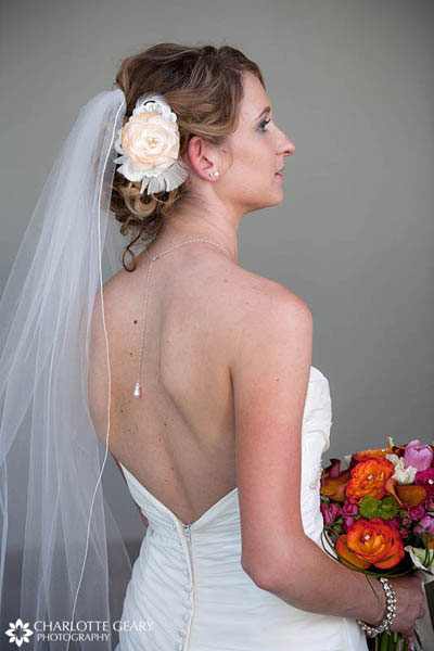 Bride with flower in her hair and a necklace with a hanging pearl down her back