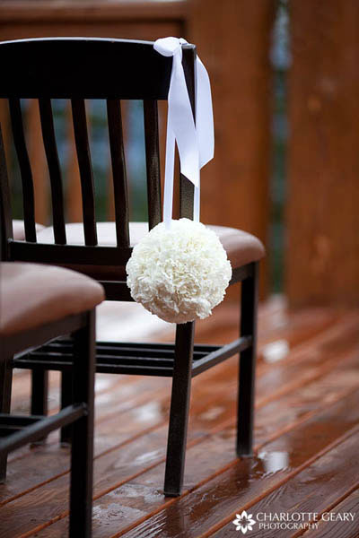 White flower ball hung from ceremony chairs