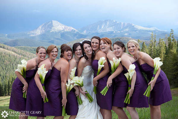 Bridesmaids in purple strapless dresses with calla lily bouquets
