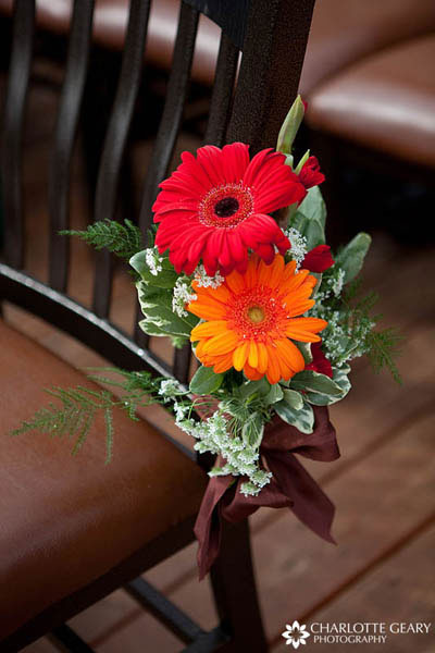 Orange and red gerbera daisies fastened to ceremony chairs