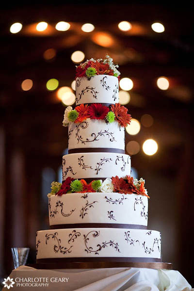 Wedding cake with brown trim and red and orange flowers