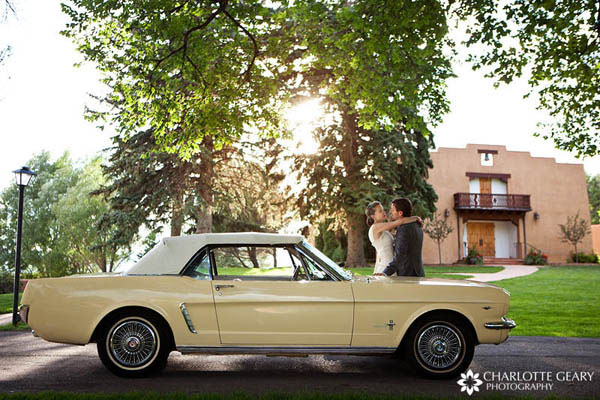 Bride and groom with antique yellow Mustang