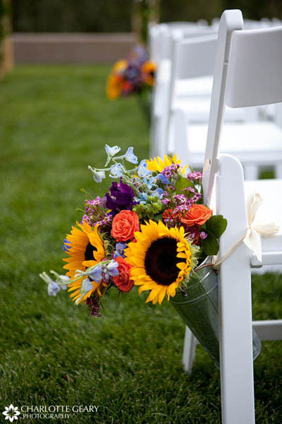 Flower arrangements in metal buckets along the aisle