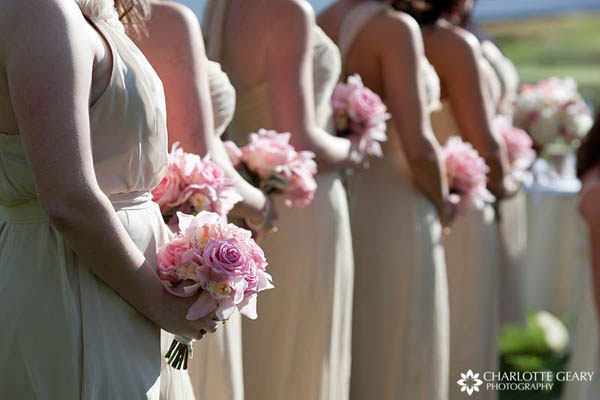 Bridesmaids in champagne dresses with pink flowers